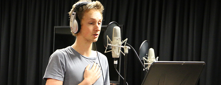 Student in front of microphone recording voiceovers